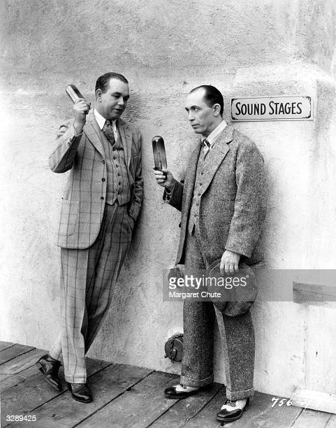 Comic actors Charles Mack and George Moran open one of Paramount's four new sound stages by breaking two photoflood bulbs The Moran and Mack company...