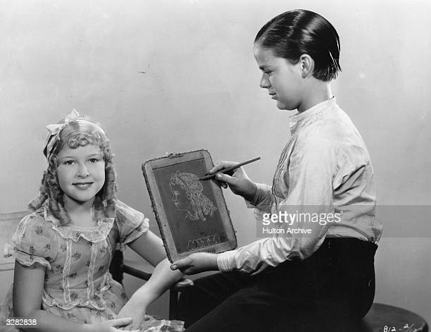 Dick Winslow is sketching on an old fashioned school slate during the filming of 'Tom Sawyer' based on the novel by Mark Twain Sitting for him is...