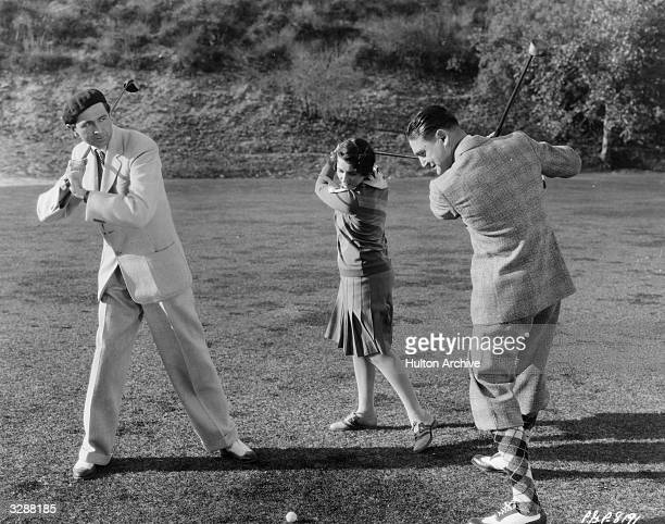 Director Malcolm St Clair and Gertrude Olmsted being given a golfing lesson by Richard Dix while filming scenes for the Paramount picture 'Sporting...