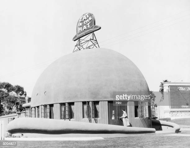 Exterior view of a woman entering the hatshaped Brown Derby restaurant on Wilshire Boulevard opposite the Ambassador Hotel in Hollywood California...