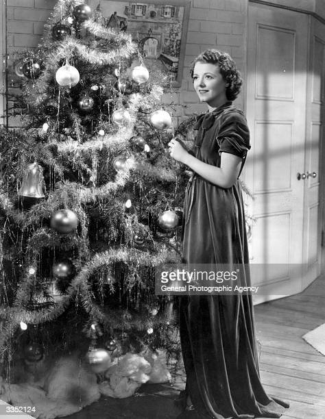 Film star Janet Gaynor winner of the first Oscar as best actress Dressed in a long velvet gown she is decorating a Christmas tree