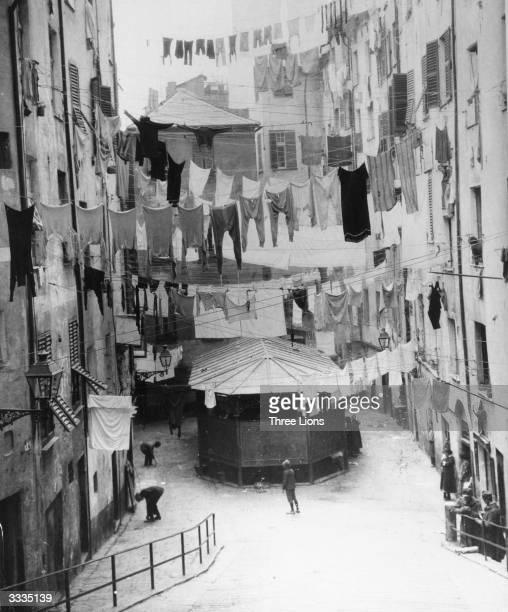 Full washing lines hanging between the houses on washday in the Piazza dei Truogoli di Santa Brigida Genoa Italy