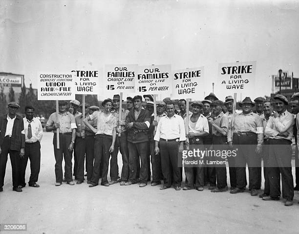 Fulllength image of a group of strikers from the Construction Workers Union holding signs while picketing for higher wages