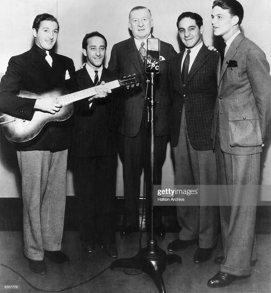 Full-length image of American actor and singer Frank Sinatra (far right) performing before a microphone with the Hoboken Four, NBC Studios.