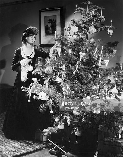 Fulllength image of British actor Elizabeth Allan standing and decorating a Christmas tree with candles and ornaments from an unidentified film She...
