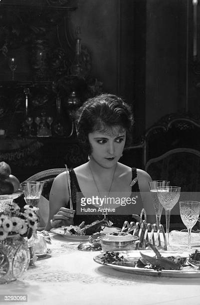 German actress Jenny Jugo sits down to dinner in a scene from one of her films