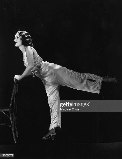 Hollywood film star Fay Wray leans on a chair to perform 'chorus routine' slimming exercises involving high kicks and stretching