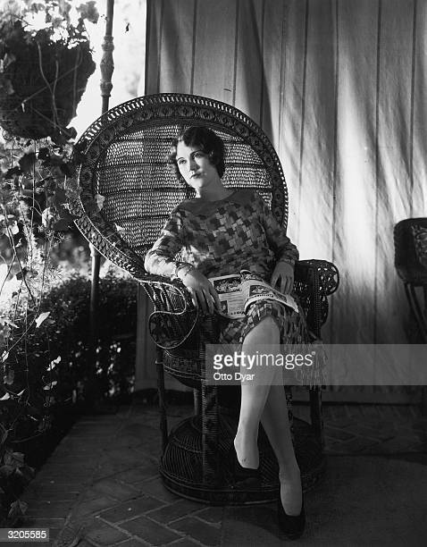 Hollywood film star Fay Wray reading a magazine in a wicker chair