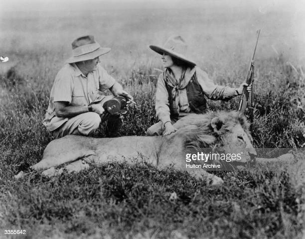 Martin Johnson and his wife pose with the body of a lion in a scene from 'Jungle Hell'