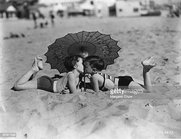Mary Ann Jackson and Wheezer two of the child stars of Hal Roach's 'Our Gang' comedy team seen kissing on the beach at Santa Monica during the making...