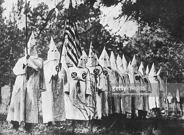 Members of the American white supremecist organisation the Ku Klux Klan dressed in ceremonial robes and hoods One is holding an American flag