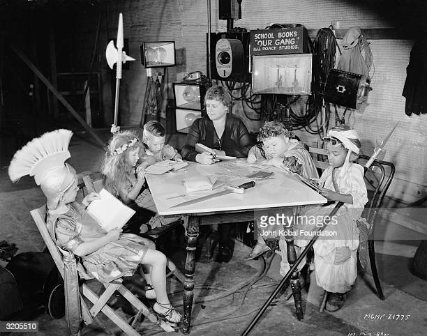 Members of the Our Gang child acting troupe catch up with their school work between takes of the latest Hal Roach comedy One of the children is...