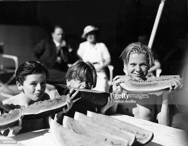 Mickey Rooney seen here with Freddie Bartholomew on his right and Jackie Cooper all young fellow artists in Hollywood consuming large quantities of...