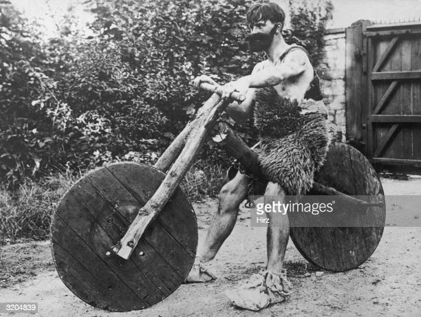 Mr R Johnstone wearing a caveman costume consisting of a false beard and an animal fur skin poses on a 'prehistoric' bicycle made of wood outdoors at...