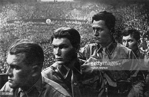 Nazi party members listening to a speech by Hitler.