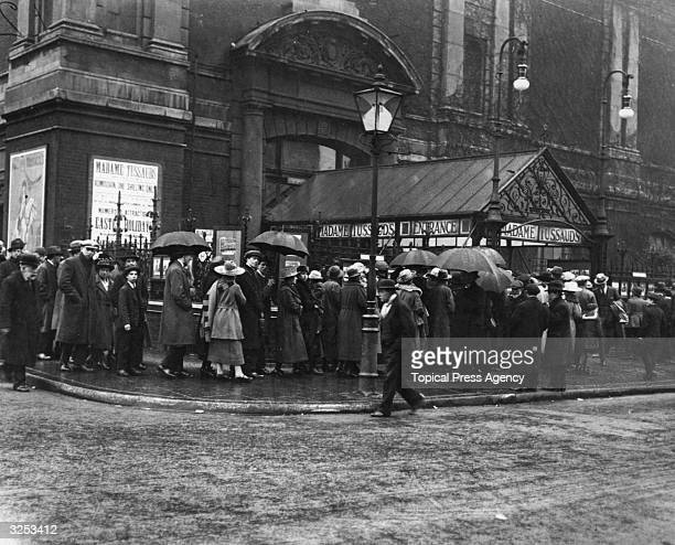 People queuing in the rain outside Madame Tussaud's Waxworks in London.