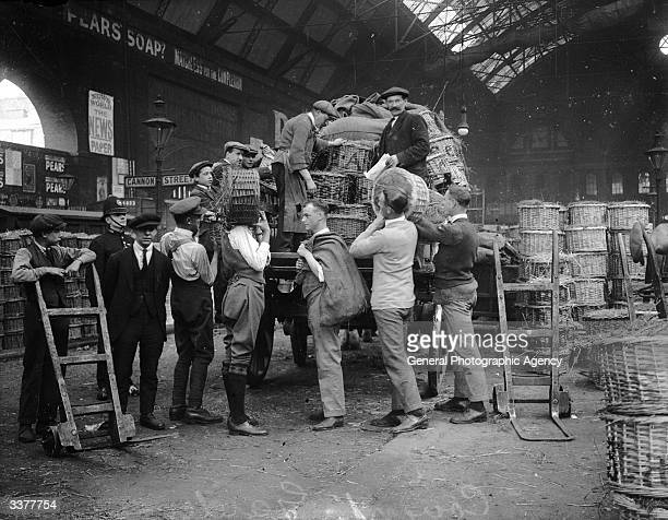 Porters at Covent Garden Market in London unloading baskets of goods from a cart