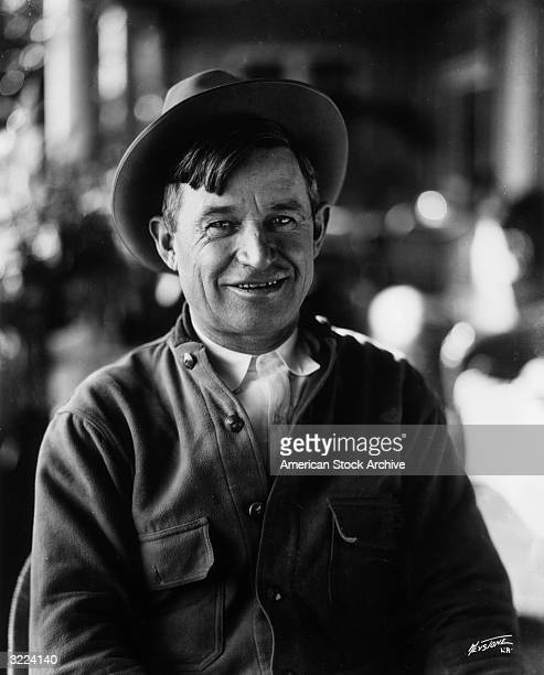 Portrait of American entertainer Will Rogers sitting and smiling He wears a hat and an overshirt