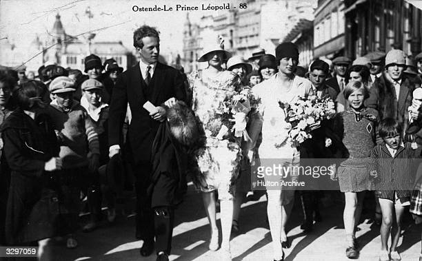 Prince Leopold later King Leopold and his wife Astrid walk in the streets of Ostende surrounded by a crowd of wellwishers