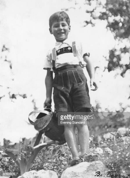 Prince Tomislav of Yugoslavia the younger brother of King Peter II is smiling at the cameraman while standing in his garden with his watering can