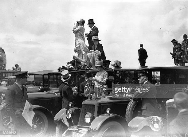 Racegoers at Ascot Some stand on their cars to get a better view