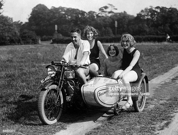Riders hitch a lift on a Triumph motorcycle and sidecar