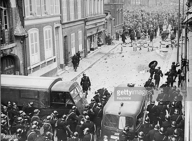 Riot police take cover behind their vans as the angry crowds hurl stones at them They have been brought into Amiens to control a demonstration by the...