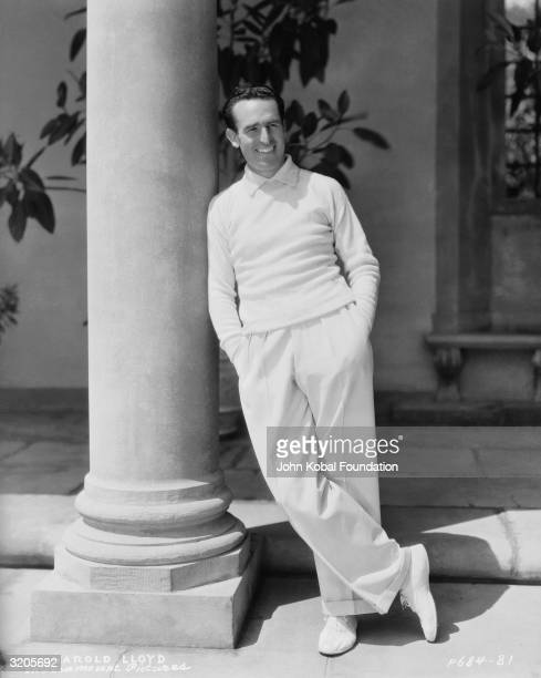 Silent comic Harold Lloyd leans against a pillar wearing an immaculate white suit