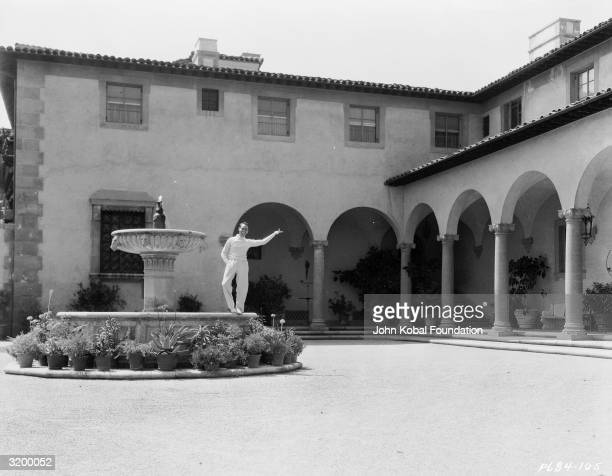 Silent screen comedian Harold Lloyd standing on a fountain in the grounds of Greenacres his palatial villa in Beverly Hills