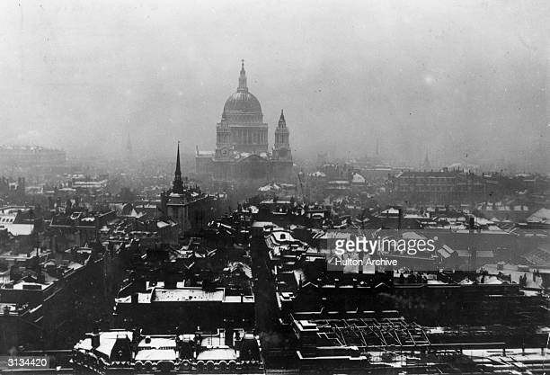 St Paul's cathedral rising above the snow covered roofs of the city of London