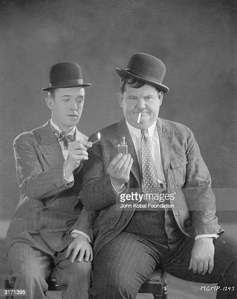 Stan Laurel offers a match to Oliver Hardy who has become exasperated with his lighter