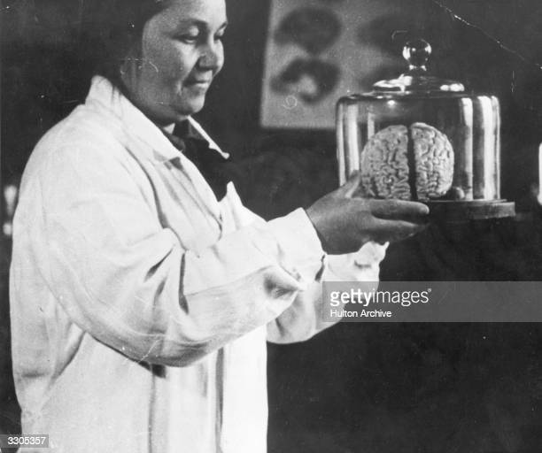 The woman in charge of the Institute for Brain Research in Moscow holds a belljar containing a brain