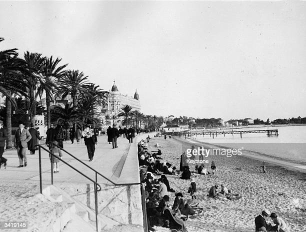 Tourists gathering on the beach and along the promenade at Cannes on the Riviera southern France