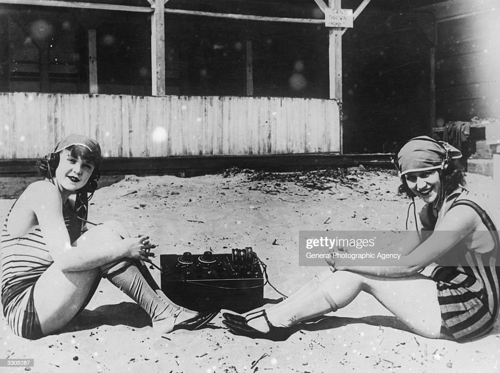 Two women listening to a BBC studio broadcast on the beach.