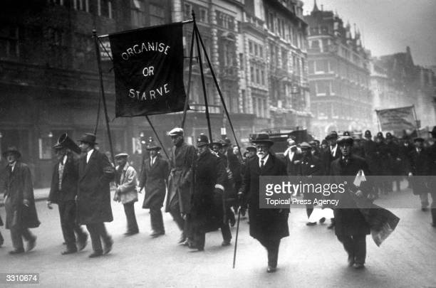 Unemployed men marching along the Thames embankment, carrying a banner reading 'Organise or Starve'.