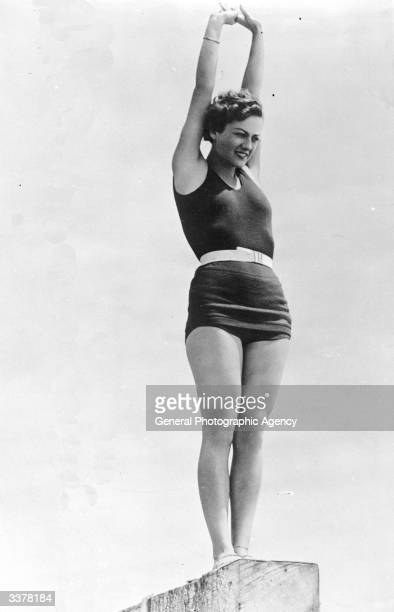 US film actress Joan Crawford standing on a divingboard wearing a swimming costume
