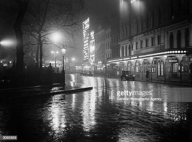 Wet pavements outside a theatre in Leicester Square London glisten in the city lights