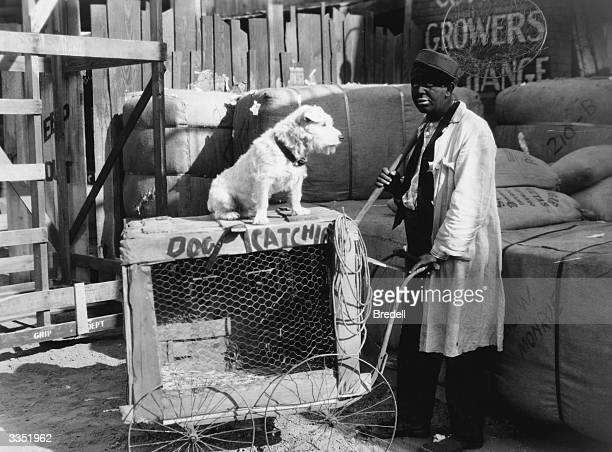White American minstrel comedian Charles Mack with an improvised mobile kennel and catching net in a scene from the film 'Two Black Crows In The AEF'