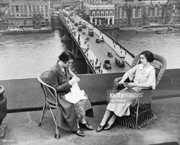 Women sit in basket chairs on a balcony overlooking London Bridge and the River Thames.