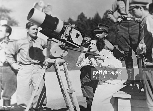 Circa 1930's Germany German film director Leni Riefenstahl looks through the lens of a film camera while being watched by uniformed Nazi officials