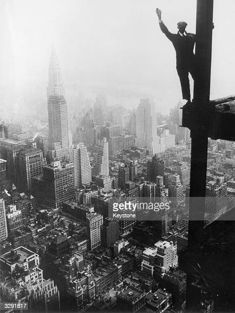 A steel worker balances on a girder during the construction of the Empire State Building in New York City The Chrysler Building can be seen in the...