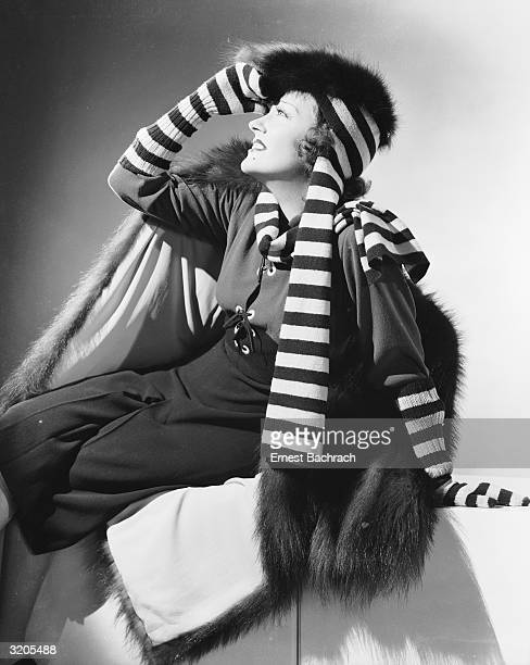 American actress Gloria Swanson wearing a fur hat and coat accessorised by a striped scarf and elbow length gloves
