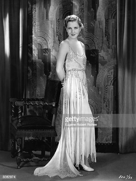 American actress Jean Arthur the stage name of Gladys Greene wearing a formal gown of white chiffon deftly trimmed with crystals and fringe