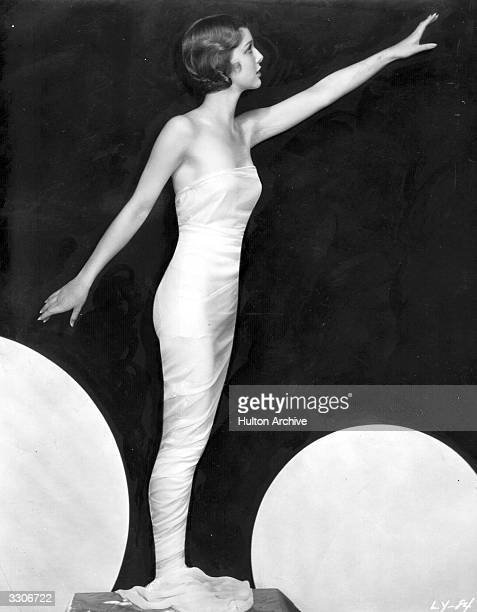 American actress Loretta Young standing with her arms stretched to front and back with satiny material draped tightly round her body