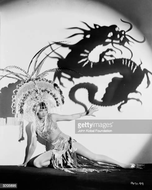 ChineseAmerican film star Anna May Wong wearing an exotic costume and headdress Above her is a projected shadow of a dragon