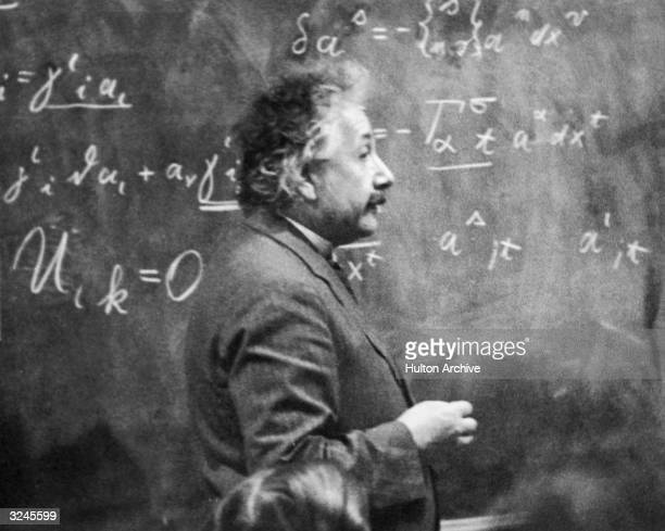 German-born physicist Albert Einstein standing beside a blackboard with chalk-marked mathematical calculations written across it.