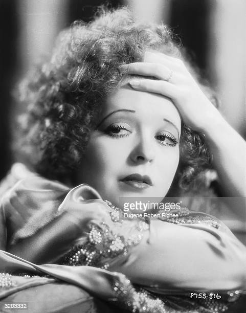 Hollywood actress Clara Bow clasps her hand to her forehead