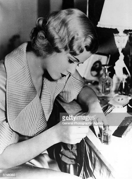 Joan Bennett the American leading lady of the 30's and 40's who was at one time married to Walter Wanger pictured sitting at her dressing table...