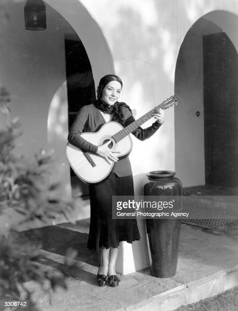 Mexican actress Lupe Velez born Guadeloupe Velez de Villalobos playing a guitar in the courtyard of a garden She will be performing a singing role in...