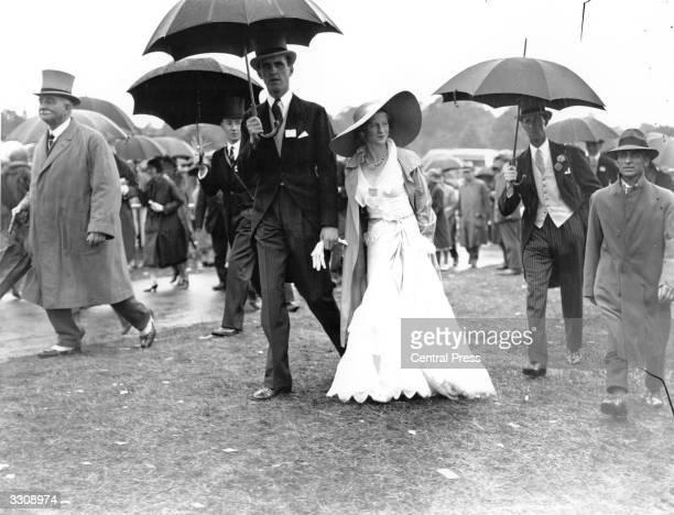 Racegoers at Ascot shelter under umbrellas from the rain.